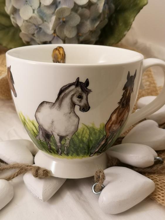 Tekopp med hästar och gräsfält. På denna bild en vit häst och en brun häst bredvid som tittar framåt. Dessutom häst på insidan av koppen.