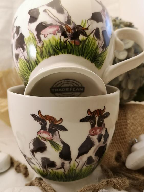 Två koppar på bilden med kor på. Framsidan har två kor bredvid varandra och baksidan visar två betande kor.