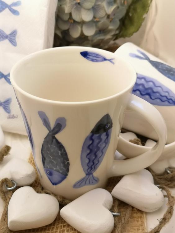 Fiskmotiv på mugg. Fiskarna har blå färg med fjäll och fenor bl.a.