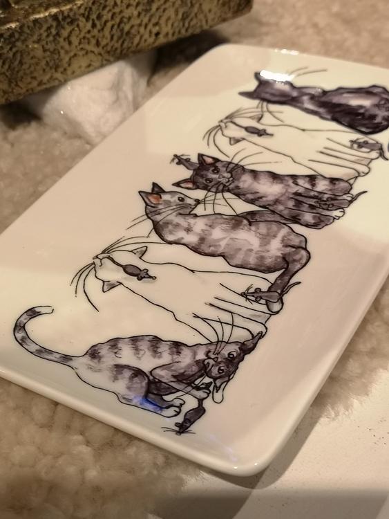 Katter och små möss på assiett i porslin.