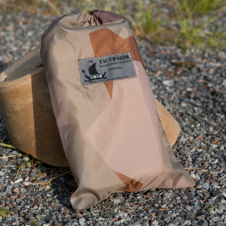 The Small Bag M90K Desert is a thinn and versatile bag for your smaller stuff, here seen with gravel background.