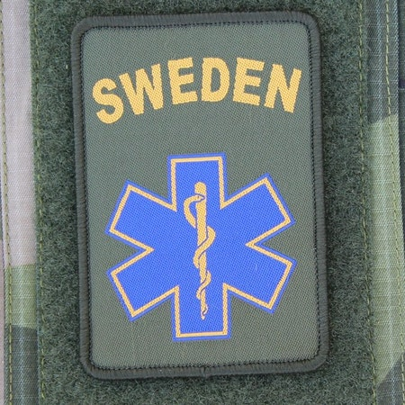 SWE MEDIC Star Hook Patch mounted on arm of a M90 camouflage jacket.