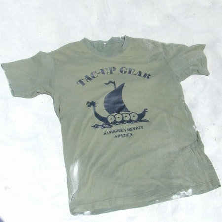 Laying in the fine white sand is a T-Shirt Khaki Green TUG.