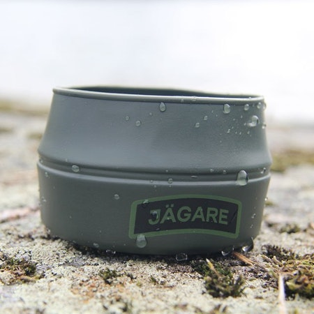 Folding Cup JÄGARE Green/Black/Green on stony lakeside rocks.