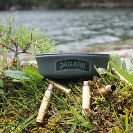 Shellcasings and a Folding Cup JÄGARE Green/Black/Green with grass leaves and water in the background.
