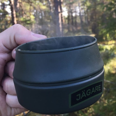 The warmth of a cup of coffee in the forest is shown when using a Folding Cup JÄGARE Green/Black/Green