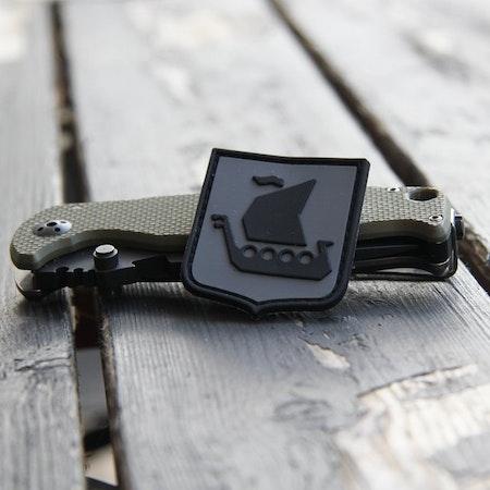 En kniv används som stöd och storleksjämförelse  vid produktfoto av en Vikingship Shield Hook PVC Black/Grey Patch.