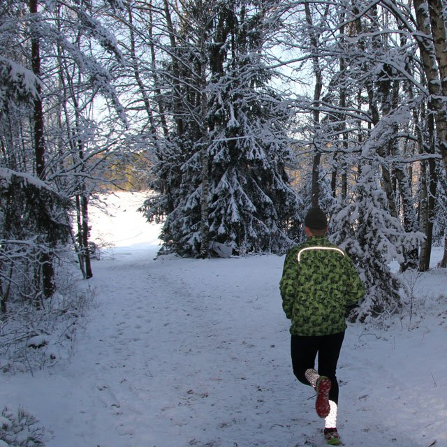 Reflective shoulder stripe showing on runner in Swedish winter scenery wearing a Running Jacket M90 MI.