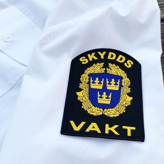 Skyddsvakt Rundad Tygmärke på ärm mot vit skjorta