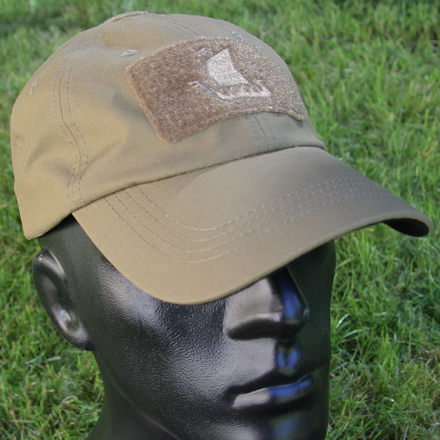 Baseball Cap Coyote with green grass background.