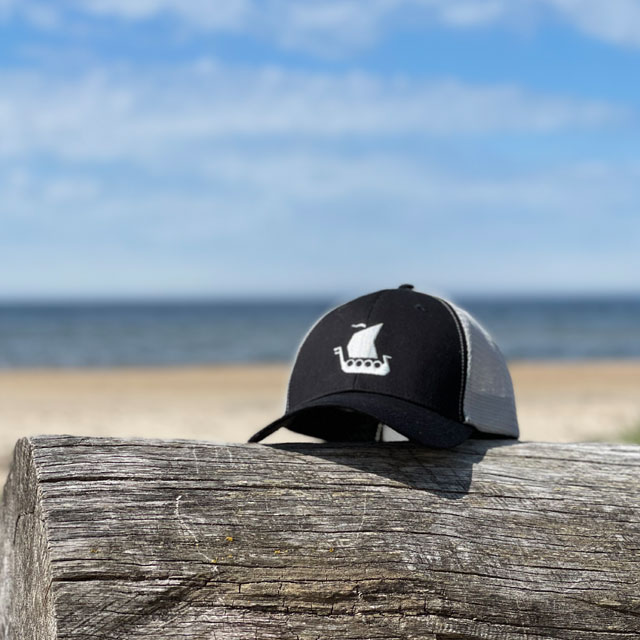 Mesh Cap Black and Grey from TAC-UP GEAR seen from the front on a log on a beach