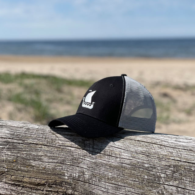 A Mesh Cap Black and Grey from TAC-UP GEAR seen from the side front on a log on a beach