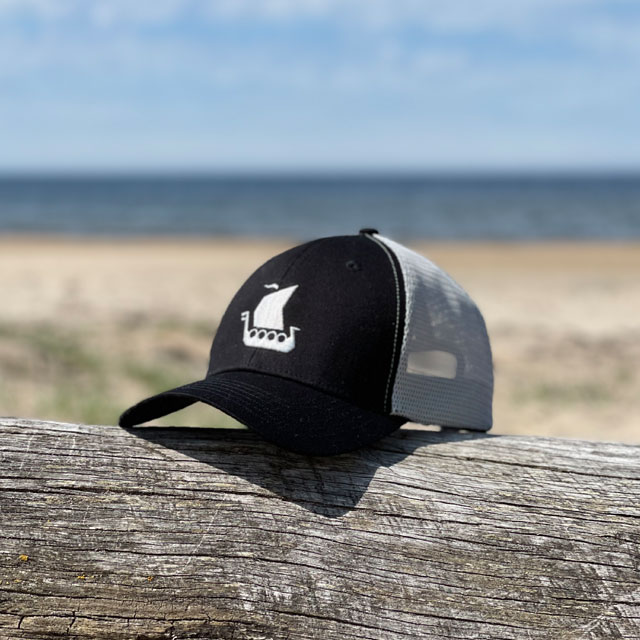 Mesh Cap Black and Grey from TAC-UP GEAR seen from the side front on a log on a beach