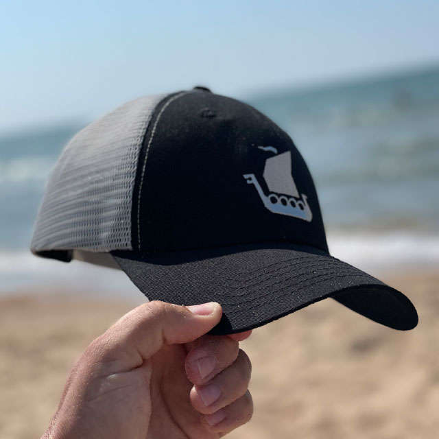 A Mesh Cap Black and Grey on the beach with ocean background