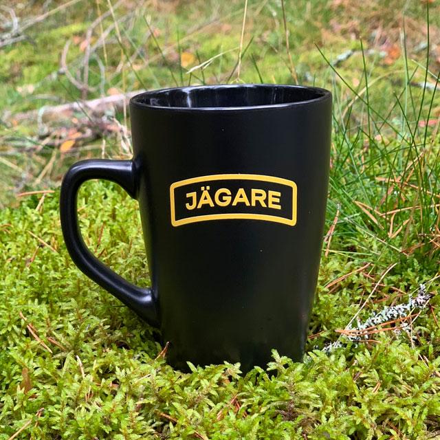 En Kaffemugg JÄGARE Black i skogen på mossa
