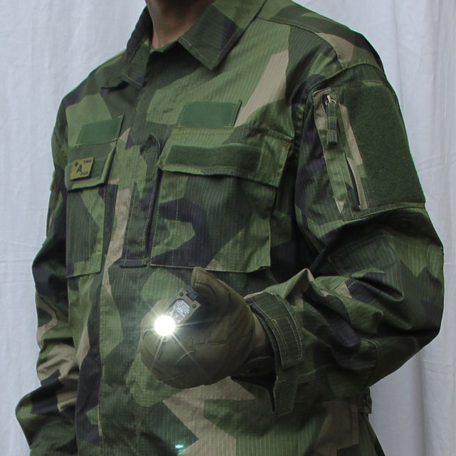 Slight sideview of a Field Shirt M90 and holding a sidewinder flashlight.