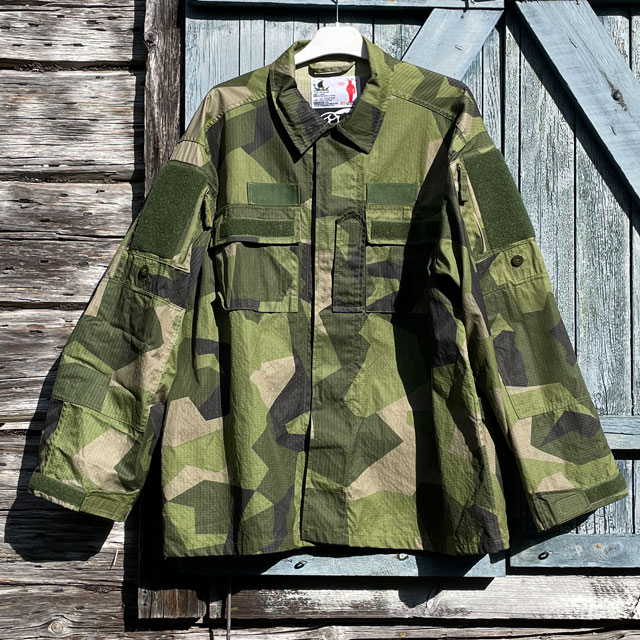 A closer look at our popular Field Shirt M90 hanging on a wooded buildning as background