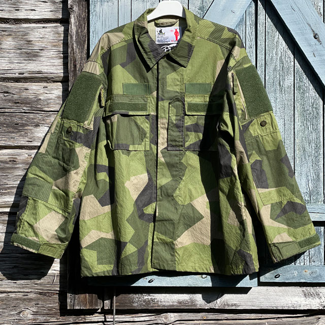 Seen full front is our popular Field Shirt M90 hanging on a wooded buildning as background