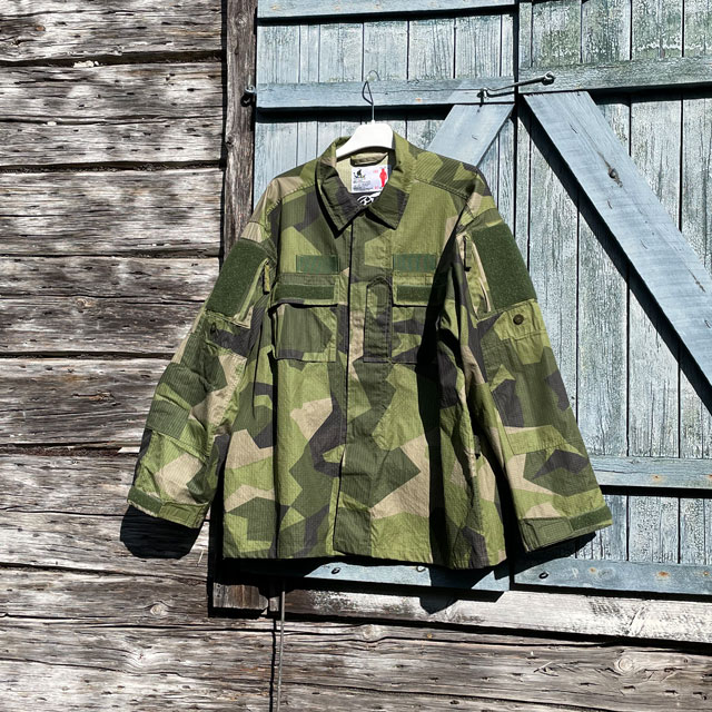 Our popular Field Shirt M90 hanging on a wooded buildning as background