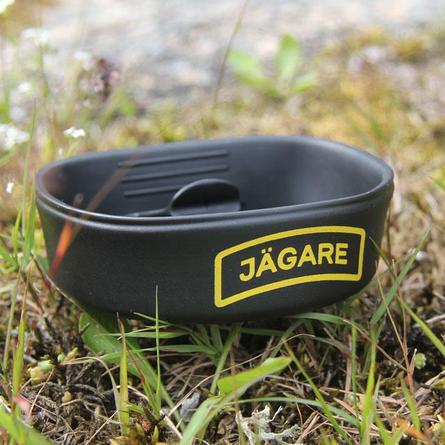 A folded Folding Cup JÄGARE Black/Yellow/Black on summer scenery ground.