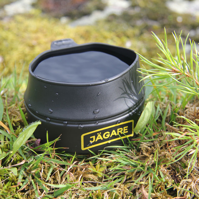 Filled to the brim the Folding Cup JÄGARE Black/Yellow/Black sits on the ground in Sweden during summer picture.