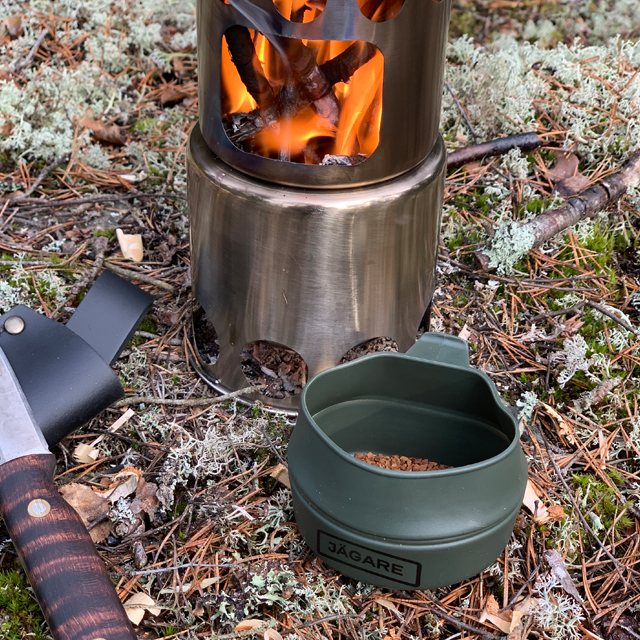 Folding Cup JÄGARE OD Black/Green/Black on the ground in Swedish forest with instant coffee in it