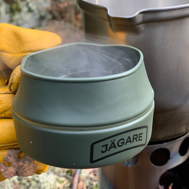 Close up on a Hot smoking coffee in a Folding Cup JÄGARE OD Black/Green/Black in the Swedish forest