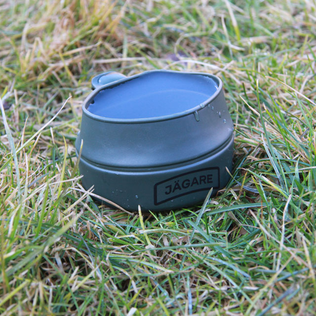 A Folding Cup JÄGARE OD Black/Green/Black filled to the brim on the grassy Swedish summer nature floor.