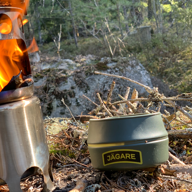 Folding Cup JÄGARE OD Yellow/Black/Yellow beside a lit stove