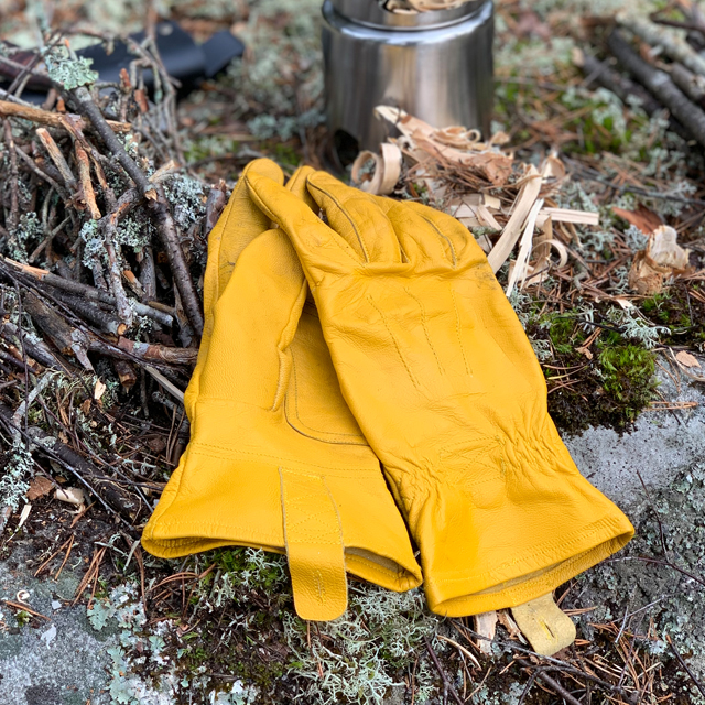 A pair of Bushcraft Leather Glove near a stove in the Swedish forest