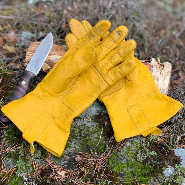 Bushcraft Leather Glove and knife lying on a stone