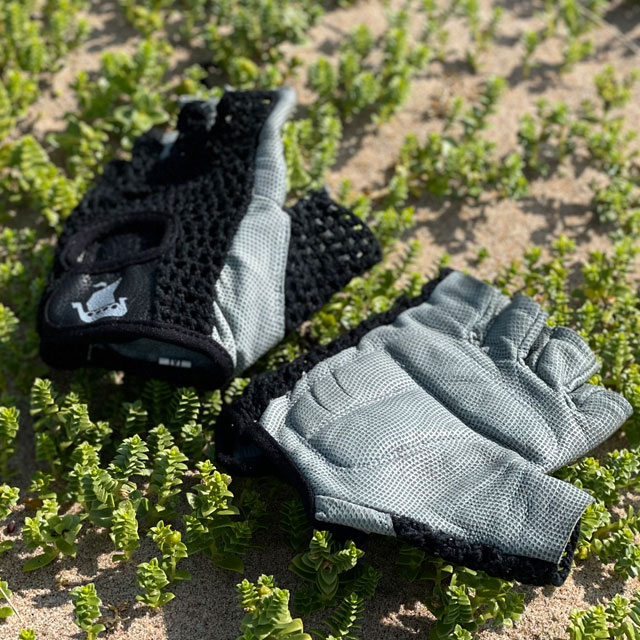 A pair of Training Glove Net Black lying flat on the sandy ground seen from a slight angle