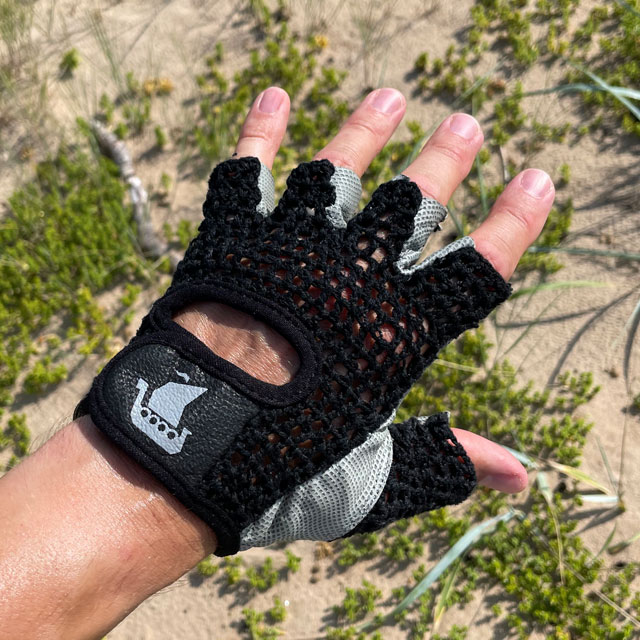 Seen from the top a Training Glove Net Black with beach sand and green background