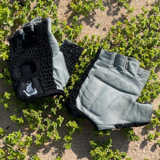 A pair of Training Glove Net Black lying flat on the sandy ground