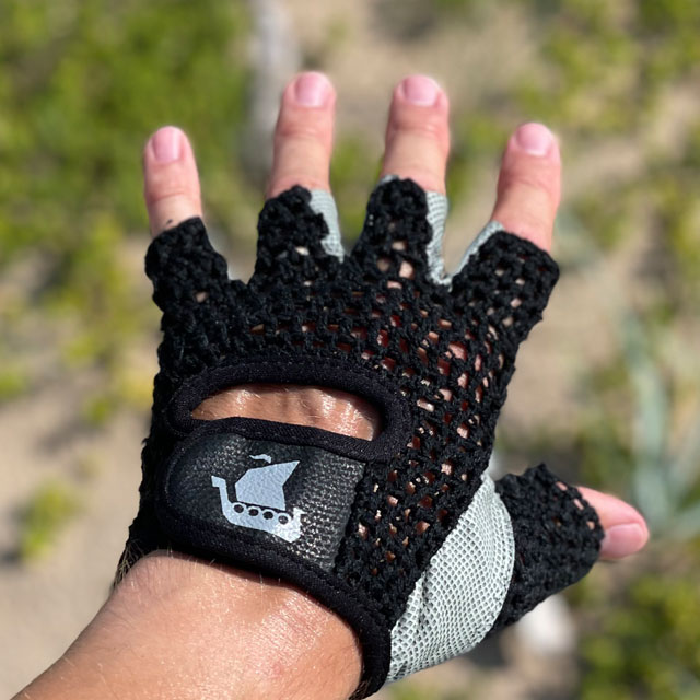 The top side of a Training Glove Net Black with beach sand and green background