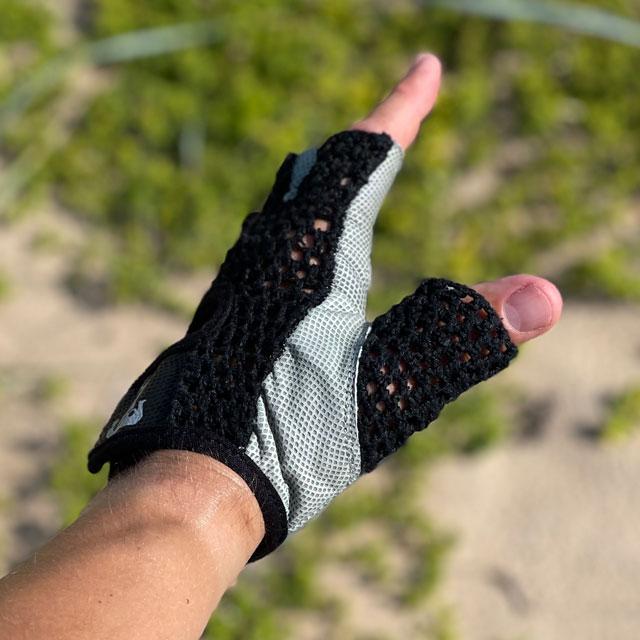 The side of a Training Glove Net Black with beach sand and green background