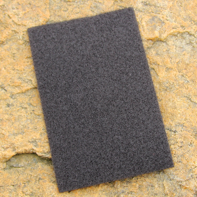 A Kardborre Panel 9x14 Greyish Black with rock background for product photo.