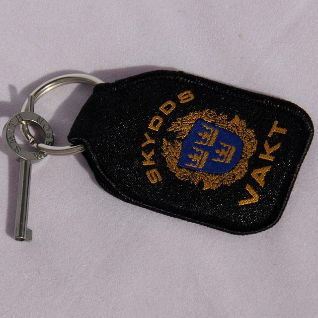 Nyckel till handfängsel monterad på silverringen på en Skyddsvakt Nyckelring.