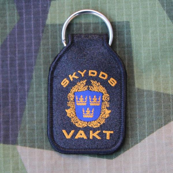 Skyddsvakt Nyckelring mot en bakgrund av M90 kamouflage.