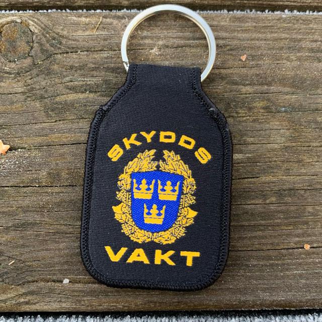 Skyddsvakt Nyckelring - M19 liggandes på planka