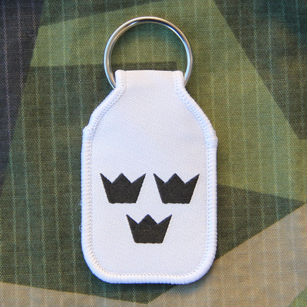 Keyring White With Crowns in a M90 camouflage background.