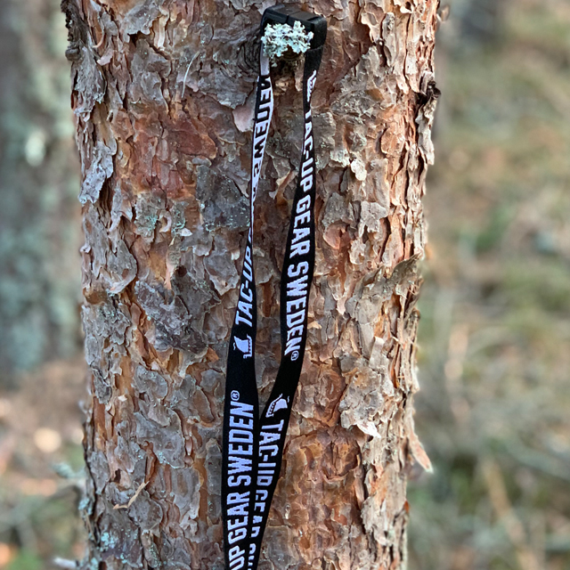 Lanyard Black/White hanging on a tree in the forest