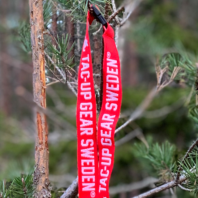 Lanyard Red/White hanging on a branch