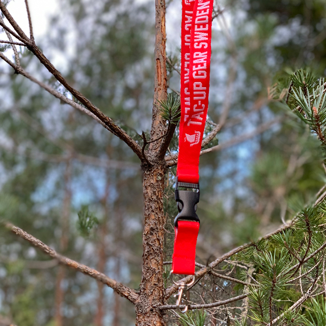Lanyard Red/White in focus hanging on a branch in the forest