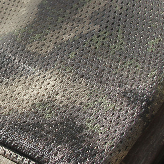 Small holes perforate the camouflage fabric on a Sniper Scarf Archipelago.