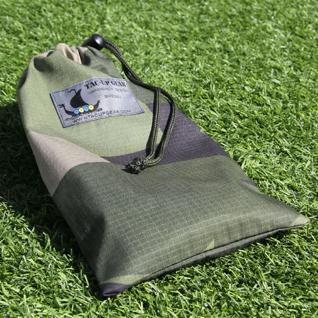 Mini Bag Ripstop M90 in the sun laying on grassy ground showing the ripstop fabric and camouflage.