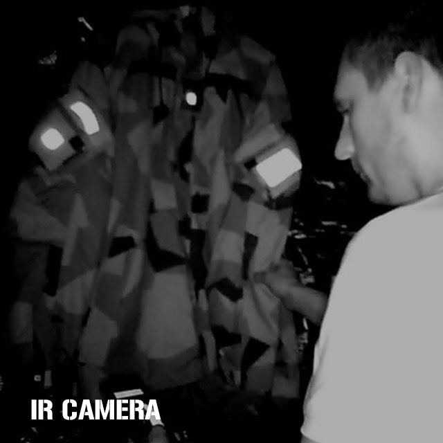 IR Camera photo in dark room showing model in plain clothes and reflective IR patches on NCWR Jacket M90