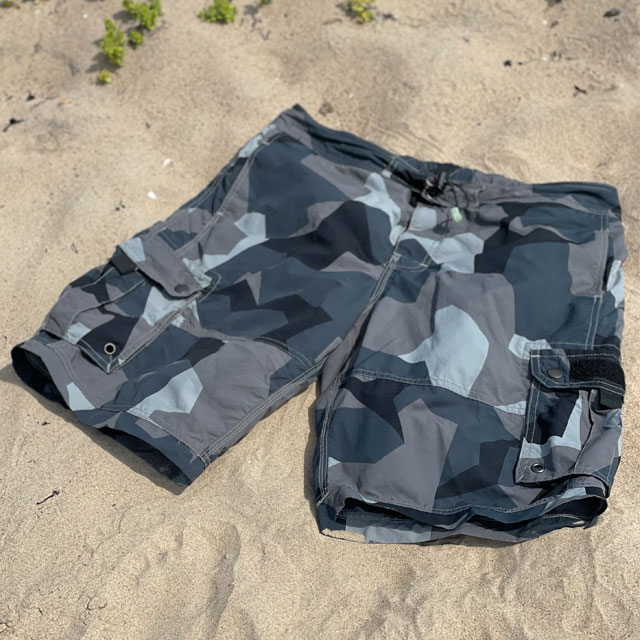 Seen slightly from the side is a pair of NEPTUNE Shorts M90 Grey laying flat in the sun