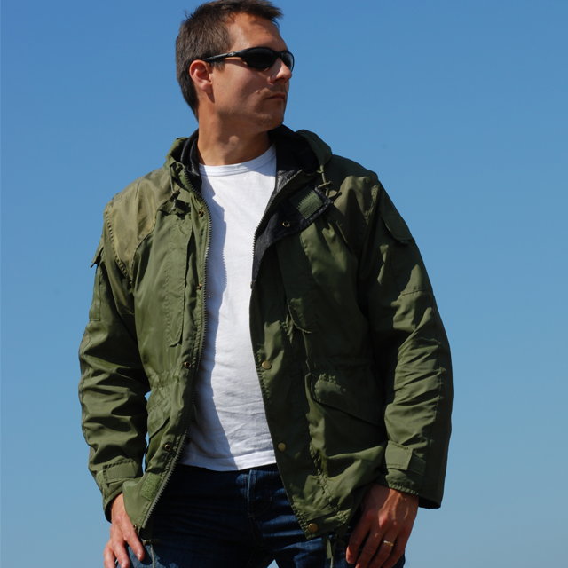 Casual open and worn Nomad Jacket Green in bright blue sky scenery.