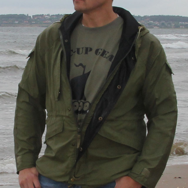 Casual open and worn Nomad Jacket Green at autumn beach scenery.